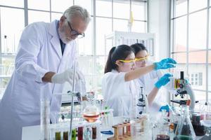 medisch onderzoek en wetenschappers werken met een microscoop en een tablet en reageerbuisjes, micropipet en analyseresultaten in een laboratorium. foto