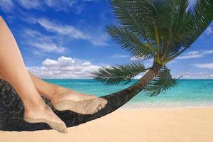 meisje bungelt haar voeten aan een palmboom foto