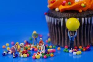 plastic mensen die een rommelige cupcake opruimen foto