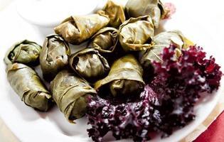 een bord heerlijke gevulde druivenbladeren met peterselie garnituur foto