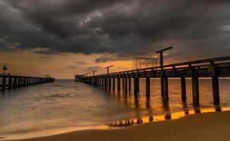 lange zeebrug in de zonsondergangtijd. foto