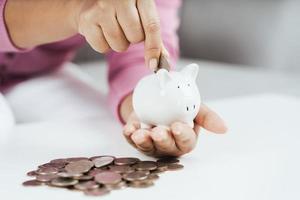 close-up van de hand van de vrouw die geldmunt in spaarvarken stopt om geld te besparen. geld besparen en financieel concept foto