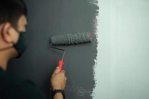 jonge man schildert een donkere kleur binnenmuur van concept werk vanuit huis foto