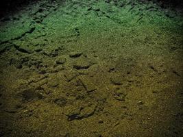 textuur van donker zand aan zee foto