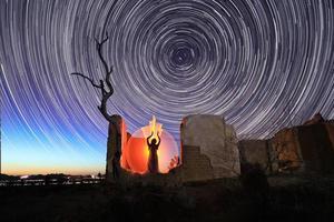 persoonslicht geschilderd in de woestijn onder de nachtelijke hemel foto