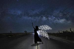 meisjeslicht geschilderd in de woestijn onder de nachtelijke hemel foto