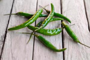 groene rauwe chili op houten achtergrond foto