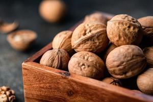 close-up van walnoten in een schelp in een houten kist op een tafel. foto