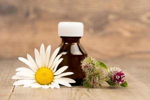 kamille en klis bloemen met etherische olie in bruine glazen flessen op houten rustieke tafel foto