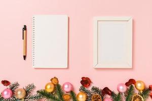 minimale creatieve platte lay van winterkerst traditionele compositie en nieuwjaarsvakantieseizoen. bovenaanzicht open mockup zwarte notebook voor tekst op roze achtergrond. bespotten en kopiëren van ruimtefotografie. foto