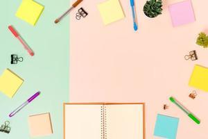 creatieve platliggende foto van een werkruimtebureau. bovenaanzicht bureau met toetsenbord, muis en open mockup zwarte notebook op pastel groen roze kleur achtergrond. bovenaanzicht mock-up met kopieerruimtefotografie.
