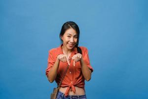 portret van een jonge aziatische dame die lacht met een vrolijke uitdrukking, laat iets geweldigs zien op lege ruimte in casual doek en kijkt naar camera geïsoleerd over blauwe achtergrond. gezichtsuitdrukking concept. foto