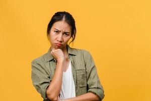 jonge Aziatische dame met negatieve uitdrukking, opgewonden schreeuwen, huilen emotioneel boos in casual kleding en kijk naar camera geïsoleerd op gele achtergrond met lege kopie ruimte. gezichtsuitdrukking concept foto