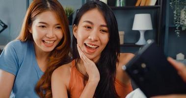 tiener aziatische vrouwen voelen zich gelukkig lachend ontspannen gebruiken smartphone video-oproep in de woonkamer thuis. vrolijke kamergenoot dames videoconferentie met vriend en familie, lifestyle vrouw thuis concept. foto