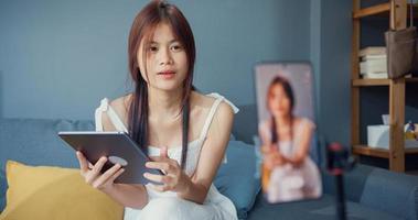 gelukkige jonge aziatische meisjesblogger voor telefooncamera gebruik tablet geniet van vraagantwoord met volgeling in woonkamer thuis. blogger activiteit levensstijl, sociale afstand coronavirus pandemie concept. foto