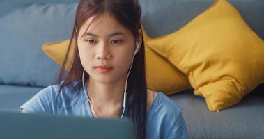 jonge Aziatische meisje tiener met vrijetijdskleding koptelefoon gebruik laptopcomputer online leren schrijven college notebook in de woonkamer in huis. isoleer onderwijs online e-learning coronavirus pandemie concept. foto
