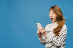 verraste jonge aziatische dame die mobiele telefoon gebruikt met positieve uitdrukking, breed glimlacht, gekleed in casual kleding en geïsoleerd op blauwe achtergrond staat. gelukkige schattige blije vrouw verheugt zich over succes. foto