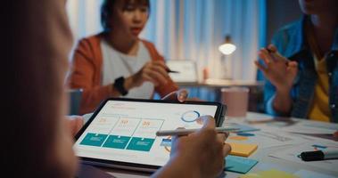 close-up azië ondernemers vergadering plan analyse statistieken brainstorm en koptekst van team houden tablet punt grafiek grafiek en werknemer noteren thuis kantoor nacht. Financiën strategie succes concept. foto
