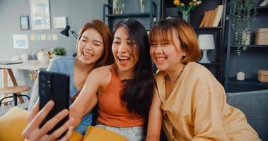 groep tiener-aziatische vrouwen die zich gelukkig glimlachen, ontspannen, gebruik een smartphone-videogesprek in de woonkamer thuis. vrolijke kamergenoot dames videoconferentie met vriend, lifestyle vrouw thuis concept. foto