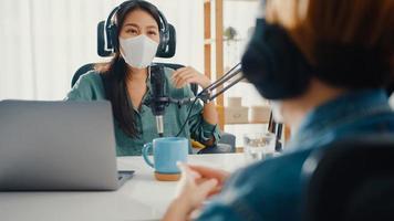 Azië meisje radio-host record podcast gebruik microfoon draag hoofdtelefoon interview gast inhoud draag masker bescherm virus gesprek praten en luisteren in haar kamer. podcast vanuit huis, coronavirus quarantaine. foto