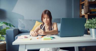 jonge Aziatische meisje tiener met casual shirt draag koptelefoon gebruik laptop leer online schrijf lezing in laptop in de woonkamer thuis. isoleer onderwijs online e-learning coronavirus pandemie concept. foto