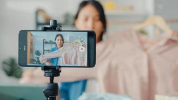 jonge aziatische dame modeontwerper met behulp van mobiele telefoon die inkooporder ontvangt en kleding laat zien die video livestreaming online opneemt in de winkel. eigenaar van een klein bedrijf, online marktleveringsconcept. foto