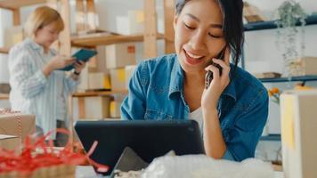 jonge Aziatische zakenvrouwen die mobiel bellen en een inkooporder ontvangen en het product op voorraad controleren op het thuiskantoor. eigenaar van een klein bedrijf, online marktlevering, lifestyle freelance concept. foto
