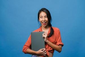 jonge aziatische dame houdt laptop vast met positieve uitdrukking, glimlacht breed, gekleed in casual kleding die geluk voelt en staat geïsoleerd op blauwe achtergrond. gelukkige schattige blije vrouw verheugt zich over succes. foto