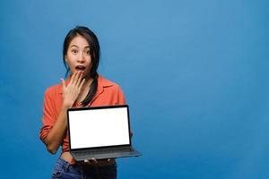jonge aziatische dame toont een leeg laptopscherm met positieve uitdrukking, glimlacht breed, gekleed in casual kleding die geluk voelt geïsoleerd op een blauwe achtergrond. computer met wit scherm in vrouwelijke hand. foto