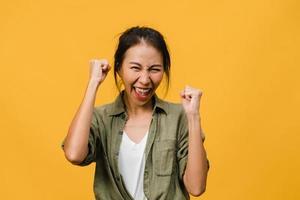 jonge aziatische dame met positieve uitdrukking, vrolijk en opwindend, gekleed in een casual doek en kijk naar de camera over gele achtergrond. gelukkige schattige blije vrouw verheugt zich over succes. gezichtsuitdrukking concept. foto