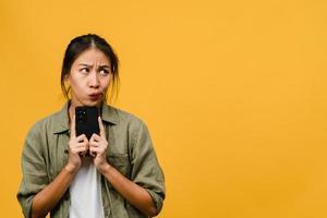 denken dromende jonge azië dame met behulp van telefoon met positieve uitdrukking, gekleed in casual doek gevoel van geluk en staan geïsoleerd op gele achtergrond. gelukkige schattige blije vrouw verheugt zich over succes. foto