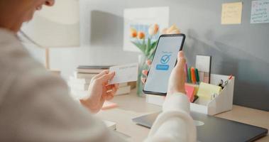 close-up jonge aziatische dame gebruikt mobiel om online winkelproduct te bestellen en rekeningen te betalen met creditcard in het interieur van de woonkamer thuis, zelfquarantaine-activiteit, leuke activiteit voor coronaviruspreventie. foto