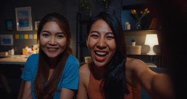 tiener azië vrouwen voelen zich gelukkig lachend selfie en kijken naar de camera met ontspannen in de woonkamer thuis 's nachts. vrolijke kamergenoot dames videogesprek met vriend en familie, lifestyle vrouw thuis concept. foto