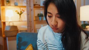 nadenkende aziatische dame die lijdt aan slapeloosheid zit 's avonds op de bank in de woonkamer met een eenzaam gevoel, verdrietig depressieve tiener brengt tijd alleen door, blijft thuis, sociale afstand, coronavirus quarantaine. foto