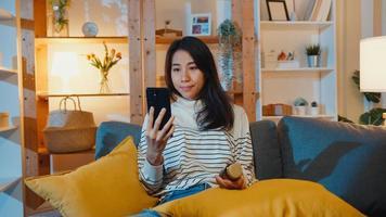 zieke jonge aziatische dame houdt medicijnen vast op de bank video-oproep met telefonisch overleg met arts thuis 's nachts. meisje neemt medicijnen in na doktersvoorschrift, quarantaine thuis, corona virus op sociale afstand. foto