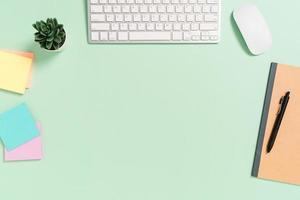 minimale werkruimte - creatieve platliggende foto van werkruimtebureau. bovenaanzicht bureau met toetsenbord, muis en boek op pastel groene kleur achtergrond. bovenaanzicht met kopieerruimte, platliggende fotografie.