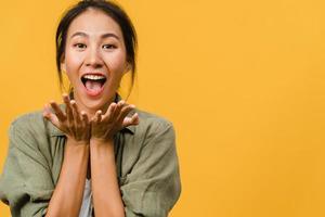 jonge Aziatische dame voelt geluk met positieve uitdrukking, vrolijke verrassing funky, gekleed in casual doek en kijkend naar camera geïsoleerd op gele achtergrond. gelukkige schattige blije vrouw verheugt zich over succes. foto