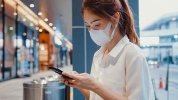 jonge Aziatische zakenvrouw in mode-kantoorkleding met een medisch gezichtsmasker met behulp van een smartphone die een sms-bericht typt terwijl ze 's nachts buiten in de stedelijke moderne stad zit. bedrijf onderweg concept. foto