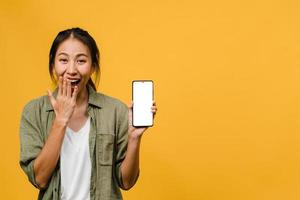 jonge aziatische dame toont een leeg smartphonescherm met positieve uitdrukking, glimlacht breed, gekleed in casual kleding en voelt zich gelukkig op gele achtergrond. mobiele telefoon met wit scherm in vrouwelijke hand. foto