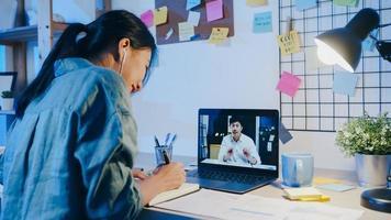 azië zakenvrouw met behulp van laptop praten met collega's over plan in videogesprek vergadering in woonkamer. 's nachts thuiswerken, werken op afstand, sociale afstand, quarantaine voor coronavirus. foto
