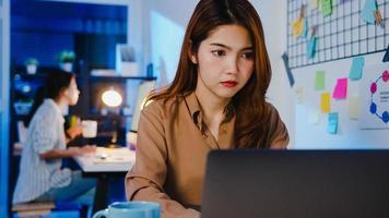 gelukkige azië zakenvrouw sociale afstand in nieuwe normale situatie voor viruspreventie tijdens het gebruik van laptop online zakelijke overuren terug op het werk in de kantoornacht. leven en werken na het coronavirus. foto