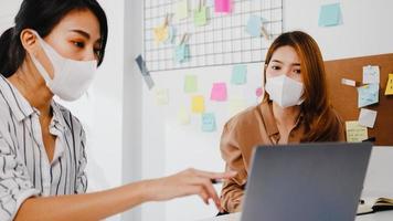 Aziatische zakenmensen die computerpresentatie gebruiken, brainstormen over ideeën over nieuwe projectcollega's en dragen een beschermend gezichtsmasker terug in een nieuw normaal kantoor. levensstijl en werk na het coronavirus. foto