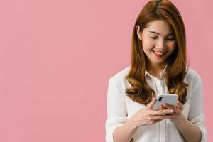 jonge aziatische dame die telefoon gebruikt met positieve uitdrukking, glimlacht breed, gekleed in casual kleding die geluk voelt en geïsoleerd op roze achtergrond staat. gelukkige schattige blije vrouw verheugt zich over succes. foto