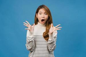 jonge aziatische dame die geluk voelt met positieve uitdrukking, vrolijke verrassing funky, gekleed in een casual doek en kijkt naar camera geïsoleerd op blauwe achtergrond. gelukkige aanbiddelijke blije vrouw verheugt zich over succes foto