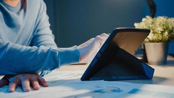 close-up azië freelance zakenman focus werk schrijven op tabletcomputer bezig met vol ruitjespapier in de woonkamer thuis overuren 's nachts, thuiswerken tijdens coronavirus pandemie concept. foto