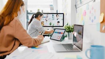 Azië zakenmensen dragen gezichtsmasker met behulp van desktop praten met collega's bespreken brainstorm over plan in videogesprek vergadering in nieuw normaal kantoor. levensstijl sociale afstand en werk na coronavirus. foto
