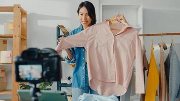 jonge aziatische dame modeontwerper met behulp van mobiele telefoon die inkooporder ontvangt en kleding laat zien die video live streaming online opneemt met camera. eigenaar van een klein bedrijf, online marktleveringsconcept. foto