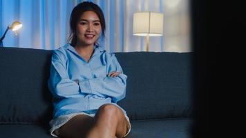 jonge aziatische dame die tv kijkt en zich gelukkig voelt, lacht terwijl ze tv-seriefilm kijkt terwijl ze 's avonds op de bank in de woonkamer zit. sociale afstand, quarantaine voor coronaviruspreventie. foto