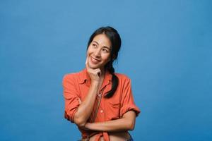 portret van jonge Aziatische dame met positieve uitdrukking, brede glimlach, gekleed in casual kleding over blauwe achtergrond. gelukkige schattige blije vrouw verheugt zich over succes. gezichtsuitdrukking concept. foto