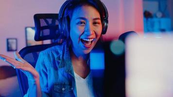 gelukkig azië meisje blogger muziek influencer gebruik smartphone uitzending opname draag hoofdtelefoon online live praten met luisterend publiek in de woonkamer thuisstudio 's nachts. inhoud schepper concept. foto